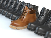 One unique brown boot in the row of black boots.  Stock Photos