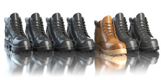 One unique brown boot in the row of black boots.  Royalty Free Stock Image
