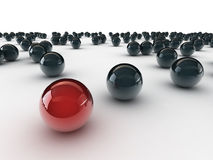 One unique red ball, among other black Royalty Free Stock Photos