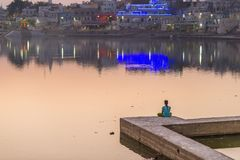 One unrecognizable person meditating on the lake bank at Pushkar, Rajasthan, India. Temples, buildings and ghats reflecting on the