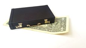 One us dollar alone lying under the suitcase stock images