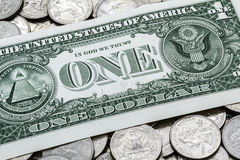 One USA Dollar Bill On A Pile Of Quarters. A close up shot of an official US one dollar bill laying on a pile of various used modern clad (non-silver Stock Image
