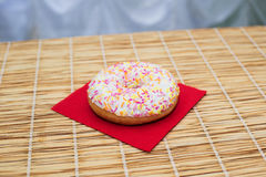One vanilla glazed donut pastry topping on red serviette Royalty Free Stock Photos