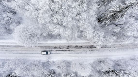 One vehicle driving through the winter snowy forest on country road. Top view. One vehicle driving through winter snowy forest on country road. Top view royalty free stock photo