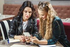 One-on-one vergadering Twee jonge bedrijfsvrouwen die bij lijst in koffie zitten Het meisje toont collegainformatie over het smar royalty-vrije stock foto