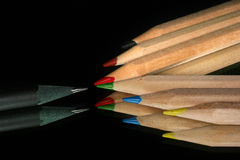 One versus all. One black pencil facing others with their reflection Stock Image
