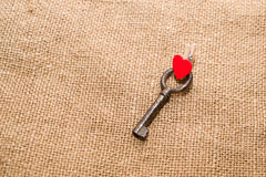 One Vintage key and a red heart on old cloth Stock Photo