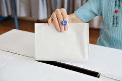 One vote. Close up of a woman's hand putting her vote in the ballot box royalty free stock photography