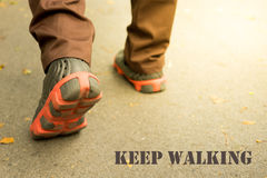 One is walking in evening light and quote 'keep walking' Royalty Free Stock Photos