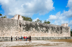 One wall at Grand Ballcourt at Chicken Itza. People visiting the Grand Ballcourt at Chicken Itza in Mexico are looking at the ancient Mayan carvings on one of stock images