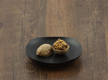One walnut shell breaking in the plate Royalty Free Stock Images