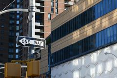 ONE WAY road sign points left on New York street. ONE WAY road sign points left on a New York City street, with high rise buildings beyond Royalty Free Stock Image