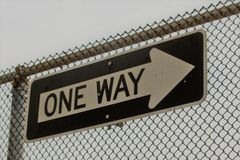 One way sign on a chain link fence Royalty Free Stock Photo