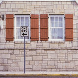 One Way Sign In Front of Windows. A one-way street sign in front of a limestone building with two white windows surrounded by wooden shutters. Shot on a medium Royalty Free Stock Image