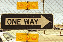 One way sign in suburban jungle. A weathered ONE WAY sign hangs on a chain-link fence between sets of orange reflectors on a roadway in the suburban jungles of Royalty Free Stock Images