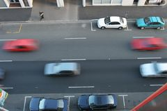 One way street. Traffic going down a mid city one way street. A few cars parked on the side of the road. Cars blurred by motion.. In Christchurch, New Zealand stock image