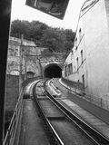 One way track. One way train going through the mountain in Lyon - black and white picture with grain filter added giving a dramatic look Stock Photo