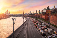 One-way traffic. Fiery sunset over the Moscow River, and one-way traffic on the embankment of the Kremlin Stock Images