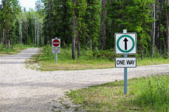 A one way and a wrong way sign by a country road intersection.  Stock Photography