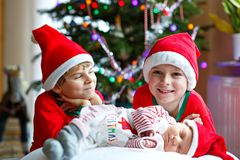 One week old newborn baby girl and two siblings kid boys in Santa Claus hats near Christmas tree with colorful garland stock photo