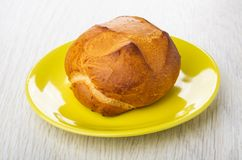 Wheat bun in yellow saucer on wooden table stock image