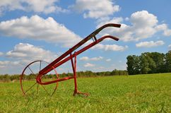 One Wheeled Garden Cultivator. A one wheeled garden cultivator parked in a field is ready to be used to till the soil Stock Photos