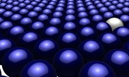 One white ball in amongst many blue balls Stock Photo