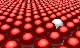 One white ball in amongst many red balls. Group of red balls with one different, white one in between - 3d rendering of a solitary white ball amongst a forest of Royalty Free Stock Image