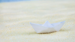 One white blurred paper ships on sand Stock Image