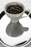 One white coffe cups with beans. One coffe cups with beans one red and other white on the metal tray Stock Images