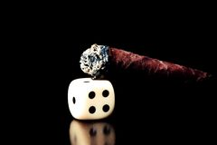 One white dice and cigar lit on old wood brown table Stock Photo
