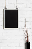 One white frame on white brick wall. The empty white frame on the wall in the composition of a vase with dried branches Stock Photography