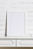One white frame on white brick wall. The empty white frame on the dresser against the wall Royalty Free Stock Image