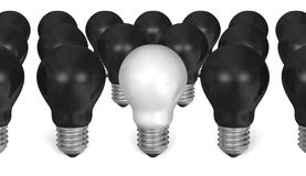 One white light bulb among many black ones Royalty Free Stock Images