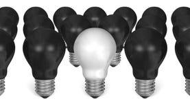One white light bulb among many black ones Royalty Free Stock Images