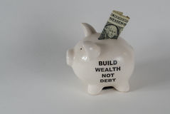 One white piggy moneybox with one dollar bill. A piggy moneybox with one dollar bill Royalty Free Stock Image