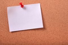 One white sticky post note pinned cork bulletin board background. One white sticky post note pinned cork bulletin board Royalty Free Stock Photography