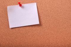 One white sticky post note pinned cork bulletin board copy space. One white sticky post note pinned cork bulletin board Stock Image
