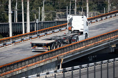 One white truck on road rides up over the bridge, industrial infrastructure, cargo transportation, delivery and shipping concept Stock Photo