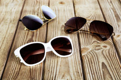 One white woman& x27;s sunglasses and two unisex sunglasses close-up Royalty Free Stock Photos