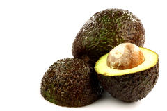One whole avocado and two halves. On a white background stock image