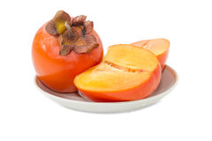One whole and cut in half of persimmon on saucer Royalty Free Stock Photography