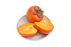 One whole and cut in half of persimmon on saucer Royalty Free Stock Photos