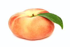 One whole flat peach with green leaf (isolated) Stock Photography