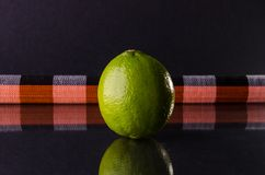 One whole lime on black background with horizontal colour strip, horizontal shot. Picture presents one whole lime on black background with horizontal colour Royalty Free Stock Photos