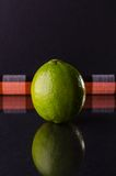 One whole lime on black background, vertical shot. Picture presents one whole lime on black background, vertical shot Royalty Free Stock Photography