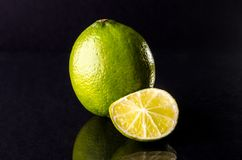 One whole lime with cuted slice on black background, horizontal shot. Picture presents one whole lime with cuted slice on black background, horizontal shot Stock Photography