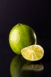 One whole lime with cuted slice on black background, vertical shot. Picture presents one whole lime with cuted slice on black background, vertical shot Stock Photo