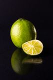 One whole lime with cuted slice on black background, vertical shot