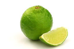 One whole lime fruit and a piece. On a white background Royalty Free Stock Photography